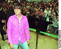 Fans welcome South Korean actor Bae Yong Joon, better known as 'Yon-sama,' upon his arrival Monday at Narita airport in Chiba Prefecture.
