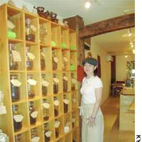 Yuko Nirei, owner of the coffee shop Cafe Sucre in Sumida Ward, Tokyo, shows off jars holding various coffee beans.