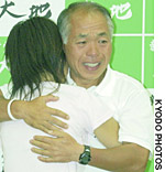 Scandal-Tainted candidate Muneo Suzuki hugs his eldest daughter while celebrating victory in Sunday's election.