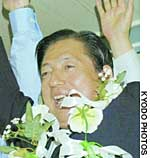 Akihiro Ota of New Komeito gives a banzai victory shout Sunday night at his election office in Kita Ward, Tokyo, while independent Eita Yashiro faces reporters after losing to Ota in the Tokyo No. 2 district.