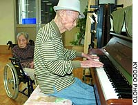 Jinzaburo Senba, 107, tickles the ivories for his wife, 100-year-old Yae, at a seniors home in Kumamoto on Tuesday. They claim to be the oldest couple in the world.