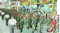 Armed members of the Ground Self-Defense Force march Saturday through a shopping mall in Sasebo, Nagasaki Prefecture.