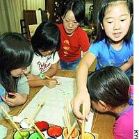 Pupils from Kyoto Municipal Gosho-Minami Elementary School try their hand at Yuzen dyeing at a studio in the city in June.