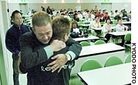 Tsutomu Iimuro, head of Sendai Drug Addiction Rehabilitation Center, hugs an addict after the man finished telling his drug-dependence story before others at the facility in Sendai in early October.