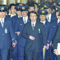 Diet security personnel escort disgraced architect Hidetsugu Aneha after he testified at a Lower House committee over the building safety scandal.