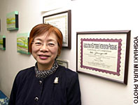 Noriko Yamaguchi, founder of Aware, poses in front of a certificate designating her as a facilitator for a domestic violence offenders' rehabilitation program.