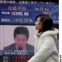 A woman walks past a giant video display in downtown Tokyo of Livedoor Co. President Takafumi Horie speaking as the Nikkei stock average plunged in the day. The selloff overwhelmed the Tokyo Stock Exchange and forced it to close earlier than usual.