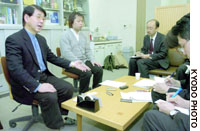 Kazunari Taira (left), a professor in the department of chemistry and biotechnology at the University of Tokyo's graduate school of engineering, responds to reporters at the university Friday after the school punished him for allegedly fabricating scientific experiments.