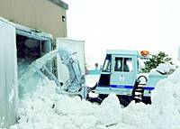 Snow is shoveled into a storage facility near a condominium complex here in February 2004. The snow is used to cool the condos in summer.