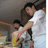 Makoto Onishi (right), crowned best pizza maker at the annual Naples pizza festival in 2003, busies himself making Neapolitan pizzas at his restaurant in the new Omotesando Hills complex in Tokyo.
