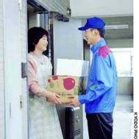 A deliveryman from Radishbo-ya Co. hands over a package of food to a customer.