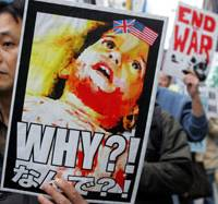 Protesters hold signs during a march through Tokyo Saturday to mark the third anniversary of the U.S.-led invasion of Iraq. About 2,000 people rallied in the capital and demanded that Japanese and other coalition troops pull out.