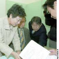 Relatives of an asbestos-linked fatality apply for state benefits at the Osaka branch of the Environmental Restoration and Conservation Agency.