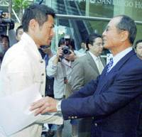 Team Japan manager Sadaharu Oh speaks with Seattle Mariners outfielder Ichiro Suzuki as they leave their hotel in San Diego after winning the World Baseball Classic.