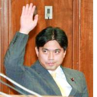 Lower House member Hisayasu Nagata raises his hand to speak during a Disciplinary Committee session.