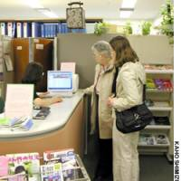 Tourists get help booking a hotel on March 9 at the Welcome Inn Reservation Center in Tokyo's Chiyoda Ward. The reservation counter will close March 31.