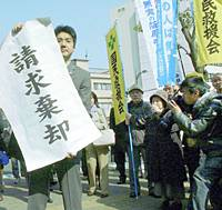 A supporter of Hiromu Sakahara, 70, who is seeking a retrial after being convicted of the 1984 murder of a liquor store owner, holds a banner Monday morning that reads 'petition rejected' in front of the Otsu District Court in Shiga Prefecture.