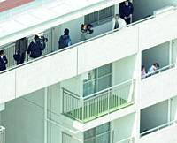 Police conduct an investigation Thursday at a 15-story condo high-rise in Kawasaki where a 9-year-old boy fell to his death on March 20 in what was initially believed to have been an accident but may have been a murder.