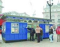 A police officer assists pedestrians in front of a police box in London's Piccadilly Circus.