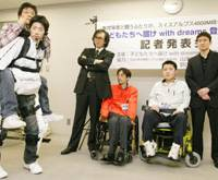 Seiji Uchida (third from right) and Kyoga Ide (second from right) look on as a robotic suit developed by Tsukuba University engineering professor Yoshiyuki Sankai (fourth from right) is demonstrated at a news conference in Tokyo last month.