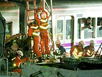 A Tokyo Fire Department crew works Wednesday evening to remove a car that was struck by a Keio Line commuter train at a grade crossing in Tokyo's Setagaya Ward.