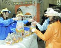Representatives of a U.S. citrus growers' association give away oranges to promote Orange Day in Tokyo's Yurakucho district last April 14.