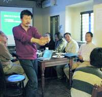 Chikara Miyachi, a researcher at the National Agency for the Advancement of Sports and Health, explains the movements of top athletes at a 'science cafe' gathering at a coffee shop in Nada Ward, Kobe.