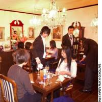 Waiters dressed as butlers serve tea and cake at the Swallowtail coffee shop in Toshima Ward, Tokyo, during a press preview in March.