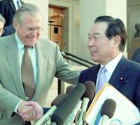 U.S. Defense Secretary Donald Rumsfeld shakes hands with Defense Agency Director General Fukushiro Nukaga in Washington on Sunday after an agreement was reached on sharing the cost of relocating 8,000 marines from Okinawa to Guam.