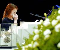 Naho Asano, who was injured and whose mother was killed in last April's train crash in Amagasaki, Hyogo Prefecture, cries during a ceremony Tuesday on the first anniversary of the accident.