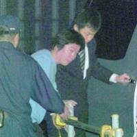 Takafumi Horie, founder of Internet firm Livedoor Co., is ushered into a car Thursday night after leaving the Tokyo Detention House following his release on bail.
