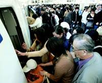People scramble aboard a train on the JR Tokaido Shinkansen Line at Tokyo Station as the busiest period of the Golden Week holidays gets under way.