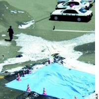 A sheet covers the wreckage of a small plane that crashed and exploded on the Tajima Airport runway here Wednesday shortly after takeoff.