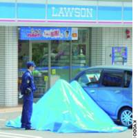 A police officer stands guard in a convenience store parking lot in Kobe where a 16-year-old girl was fatally stabbed Monday morning.