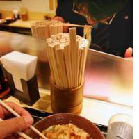 Customers eat 'udon' noodles using disposable chopsticks at a diner in Tokyo.