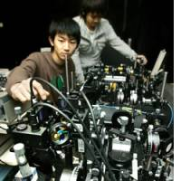 Students work on an experimental prototype for a quantum-particle computer at Hokkaido University.
