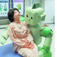 The RI-MAN, a nursing robot equipped with precision pressure sensors, lifts a human dummy during a demonstration in March.