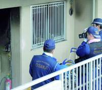 Police check the entrance of a condominium in Izumi, Osaka Prefecture, on Saturday where two boys and their infant sister were killed by a fire the day before.