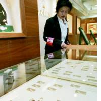 A salesclerk at the Hankyu department store in Osaka looks at an empty showcase Sunday after someone made off with hundreds of expensive watches.