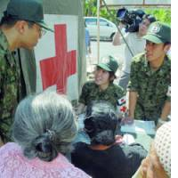 Self-Defense Forces personnel take notes at their clinic in Bantul, Indonesia, on Saturday as residents hit by the deadly May 27 earthquake explain their medical needs.