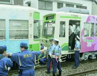 Police inspect a trolley car accident Tuesday morning in Kita Ward, Tokyo, that left 25 passengers and an official of the Arakawa Tram Line injured.