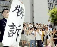 A supporter of 13 plaintiffs infected with the hepatitis C virus from tainted blood products holds up a sign declaring victory in their lawsuit as others applaud Wednesday outside the Osaka District Court.