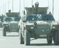 A Convoy of a light-armored vehicles of the Ground Self-Defense Force travel along a road near the camp in Samawah, southern Iraq, in April.