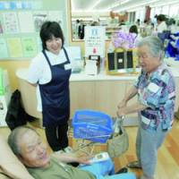 An elderly couple relax Saturday at a Lawson Inc. test outlet catering to the elderly.   KYODO PHOTO