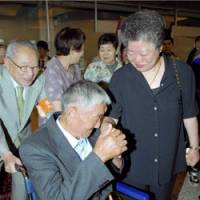 Yoshiteru Nakagawa, who went missing on Sakhalin after World War II, meets his younger sister, Tomiko Orui, for the first time at Shin Chitose Airport in Hokkaido on Sunday. | KYODO PHOTO