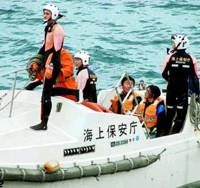 Scuba divers sit in a Japan Coast Guard boat after being rescued Monday morning.   JAPAN COAST GUARD PHOTO / KYODO