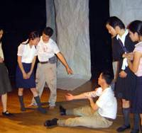 HIGH SCHOOL nurses tend their first patients in 'Okinawa 1945,' a play by Alice Shikina. | PHOTO COURTESY OF TOM TSE / KYODO