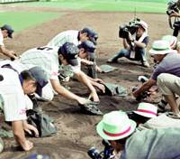 A shot of the documentary 'Kokoyakyu: High School Baseball' shows players on a losing team taking dirt from Koshien Stadium in Nishinomiya, Hyogo Prefecture, as a souvenir from the revered tournament. | PHOTO COURTESY OF PROJECTILE ARTS INC./KYODO