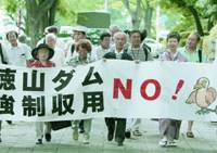 Plaintiffs in a lawsuit demanding that the state revoke permission to build the Tokuyama Dam in Ibigawa, Gifu Prefecture, head to the Nagoya High Court with a banner reading 'Say 'No!' to the Tokuyama Dam' Thursday.   KYODO PHOTO