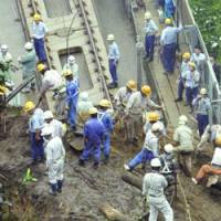 Workers clear mud Friday from the Kyushu Shinkansen Line after a predawn slide closed the section. Operations resumed in the early afternoon. | KYODO PHOTO
